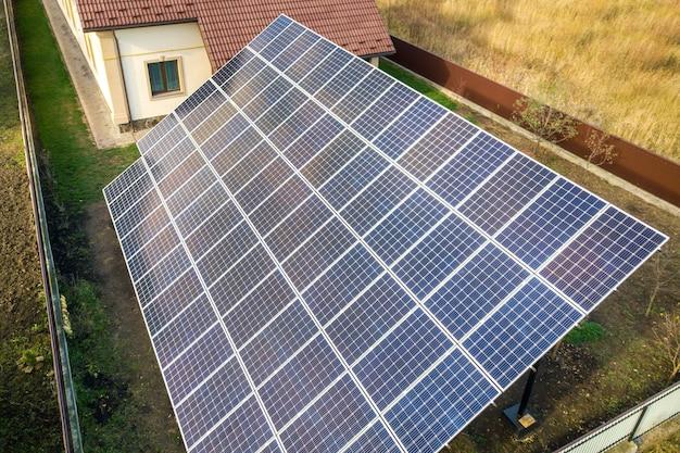 Luchtfoto van grote blauwe zonnepaneel geïnstalleerd op grondstructuur in de buurt van prive-woning. Premium Foto