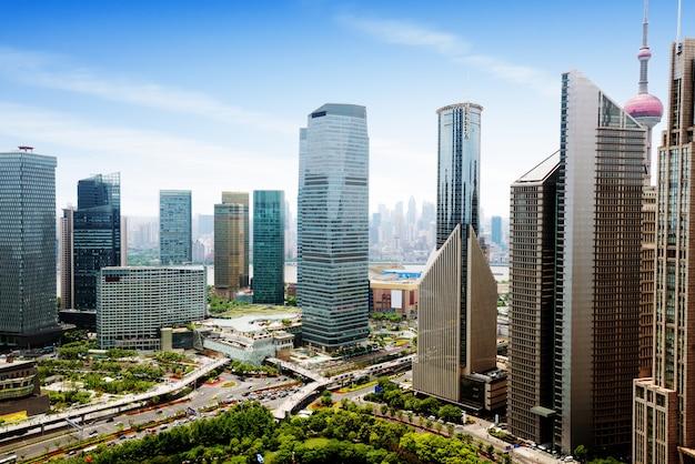 Luchtfoto van het centrale zakendistrict met hoge dichtheid in shanghai. hoogbouw kantoorgebouwen en wolkenkrabbers met glazen oppervlak. stedelijke wegen met meerdere rijstroken en groen stadspark. shanghai, china Premium Foto