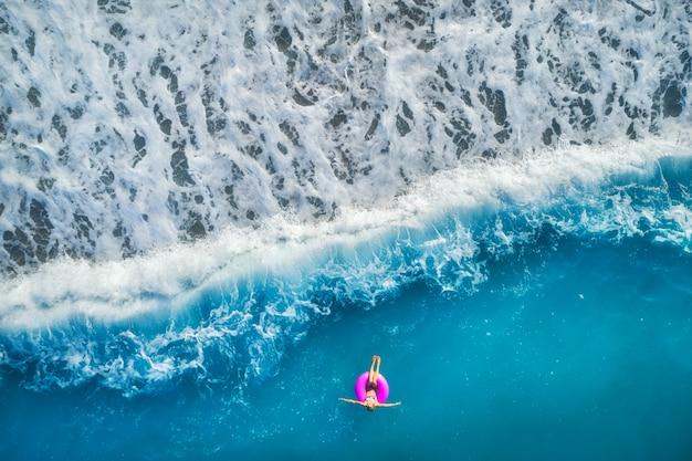 Luchtfoto van jonge vrouw zwemmen op de roze zwemring Premium Foto