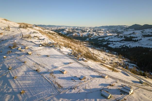 Luchtfoto van klein dorp met verspreide huizen op besneeuwde heuvels in de winter Premium Foto