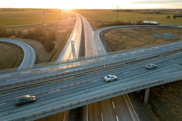 Luchtfoto van moderne snelweg weg kruispunt bij zonsopgang op landelijk landschap en het verhogen van de zon drone fotografie. Premium Foto