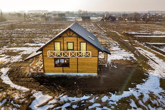 Luchtfoto van nieuwe houten ecologische traditionele huis cottage van natuurlijke hout materialen met steile grind dak in aanbouw op landelijk landschap Premium Foto