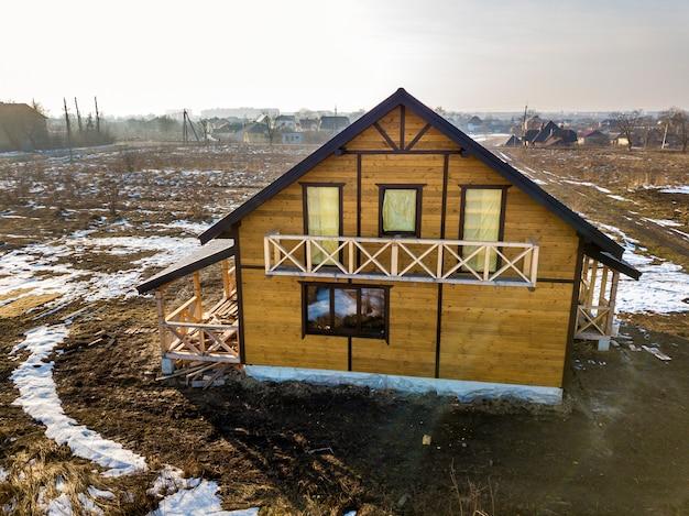 Luchtfoto van nieuwe houten ecologische traditionele huis cottage van natuurlijke hout materialen met steile grind dak in aanbouw op winter landschap achtergrond. Premium Foto