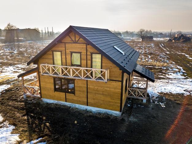 Luchtfoto van nieuwe houten ecologische traditionele huis huisje van natuurlijke hout materialen met steile shingle dak in aanbouw op landelijke winterlandschap Premium Foto