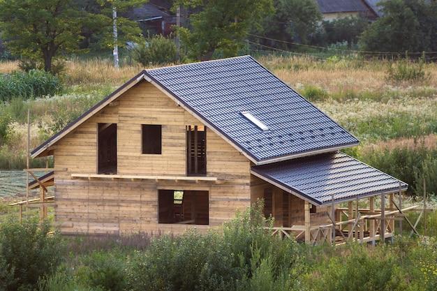 Luchtfoto van nieuwe houten ecologische traditionele huis huisje van natuurlijke hout materialen met zoldervloer, veranda, balkon en schindeldak in aanbouw in landelijk gebied. Premium Foto