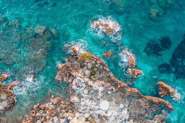 Luchtfoto van rotsen onder turquoise water Gratis Foto