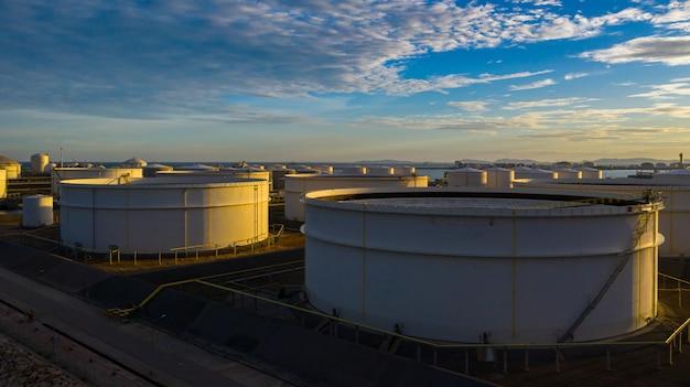 Luchtfoto van tankterminal met veel olie-opslagtank en petrochemische opslagtank bij zonsondergang, industriële tankopslag luchtfoto. Premium Foto