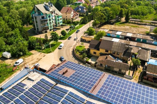 Luchtfoto van veel fotovoltaïsche zonnepanelen gemonteerd op het dak van een industrieel gebouw. Premium Foto