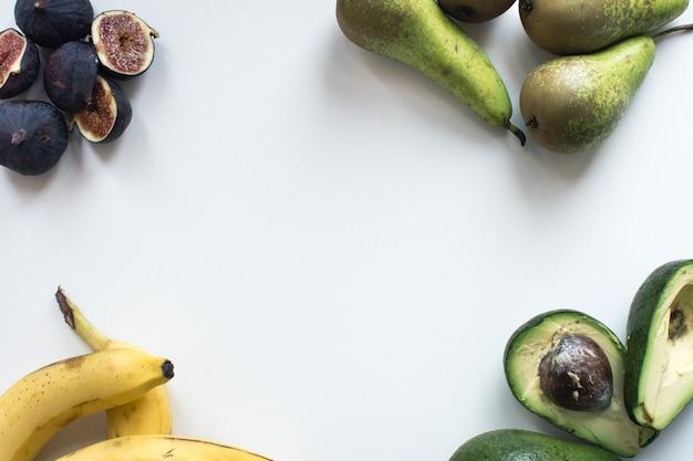 Luchtfoto van verse vijgen, bananen, peren en avocado's op een witte achtergrond Gratis Foto