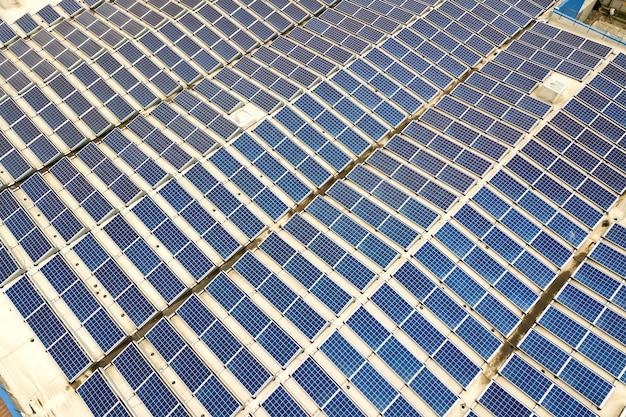 Luchtfoto van zonne-energiecentrale met blauwe fotovoltaïsche panelen gemonteerd op het dak van een industrieel gebouw. Premium Foto