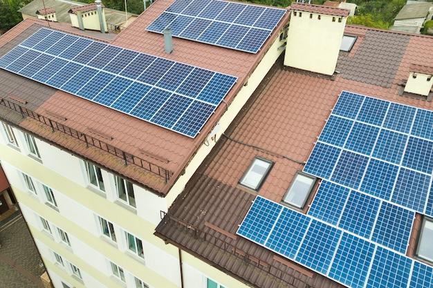 Luchtfoto van zonne-energiecentrale met blauwe fotovoltaïsche panelen gemonteerd op het dak van het flatgebouw. Premium Foto