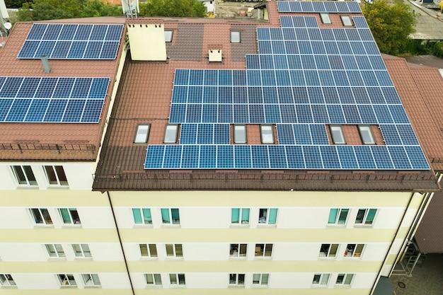 Luchtfoto van zonne-energiecentrale met blauwe fotovoltaïsche panelen gemonteerd van flatgebouw dak. Premium Foto