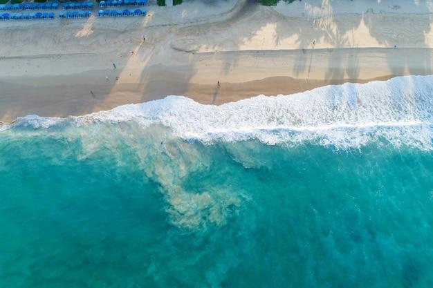 Luchtfoto zandstrand en golven prachtige tropische zee in de ochtend zomerseizoen afbeelding door luchtfoto drone schot, hoge hoek bekijken top down. Premium Foto