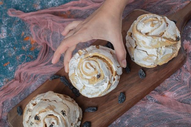 Luchtige meringue muffins met zwarte droge druiven op tafel. Gratis Foto