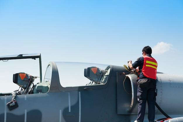 Luchtmachtpersoneel vult brandstof bij naar f16 van olie bij koninklijke luchtmacht Premium Foto