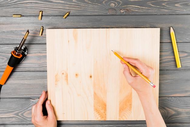Luchtmening die van hand op houten raad over lijst trekken Gratis Foto