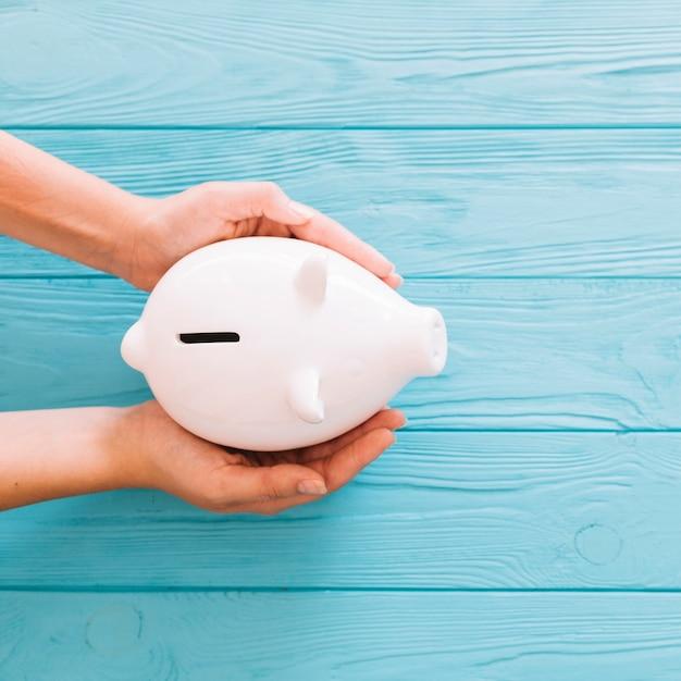 Luchtmening die van hand witte piggybank op houten blauwe achtergrond beschermen Gratis Foto