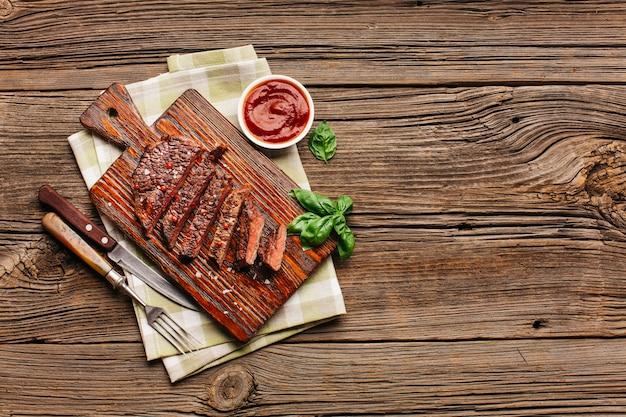 Luchtmening van gebraden lapje vlees met basilicumbladeren en saus op houten bureau Gratis Foto