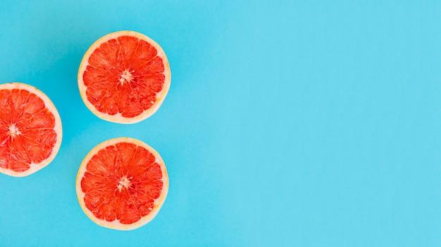 Luchtmening van grapefruitplakken op blauwe achtergrond Premium Foto