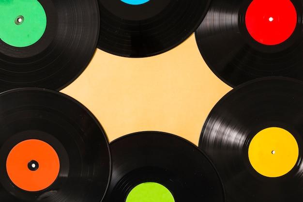 Luchtmening van kleurrijk zwart vinylverslag op beige achtergrond Gratis Foto