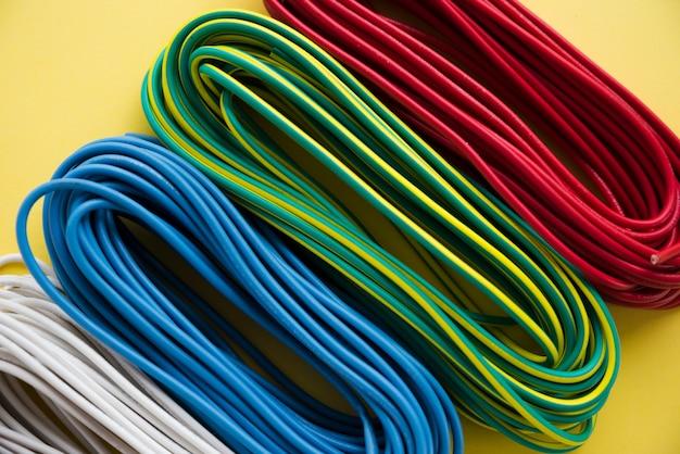 Luchtmening van kleurrijke elektrische draadbundel op gele oppervlakte Gratis Foto