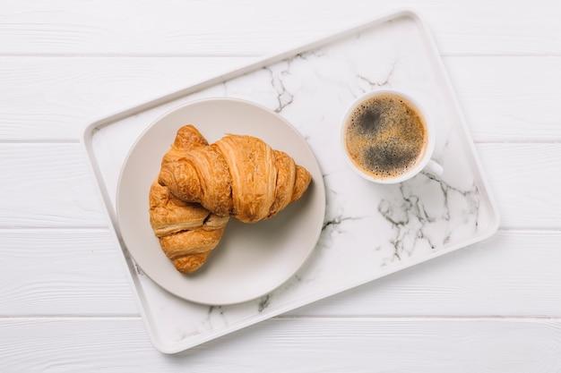 Luchtmening van koffiekop en plaat van croissantbrood in dienblad Premium Foto