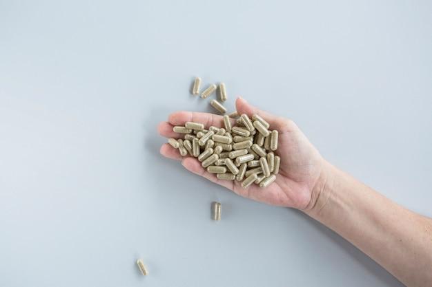 Luchtmening van pillen in de hand van de persoon tegen grijze achtergrond Premium Foto