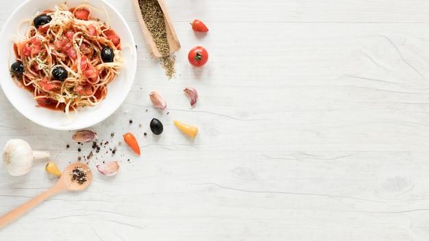 Luchtmening van smakelijke spaghettideegwaren en verse aromatische ingrediënten op lijst Gratis Foto