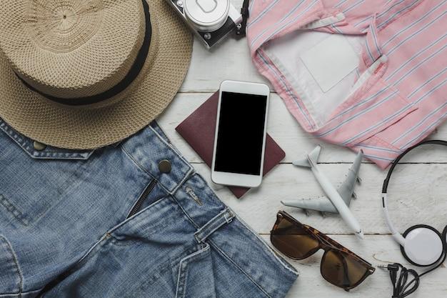 Luchtmening van toebehoren die vrouwen kleden om met technologie achtergrondconcept te reizen de essentiële punten voor reiziger of tiener en de volwassene treffen aan vakantiereis voorbereid verscheidene voorwerpen op modern wit hout. Premium Foto