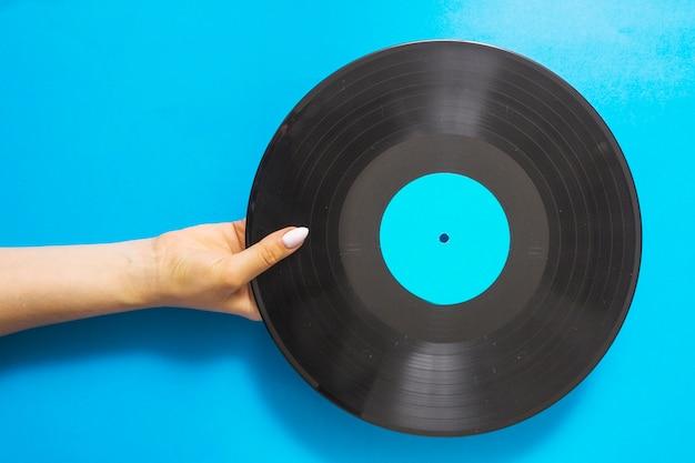 Luchtmening van vrouwelijke handen die vinylverslag op blauwe achtergrond houden Gratis Foto