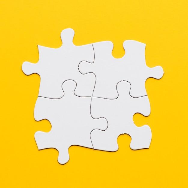 Luchtmening van witte gezamenlijke puzzel op gele achtergrond Gratis Foto