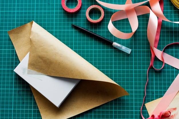 Luchtmeningsclose-up van verpakkende doos op groene besnoeiingsraad Gratis Foto