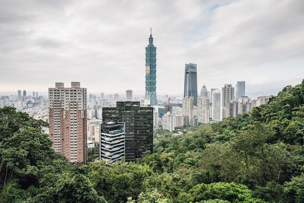 Luchtpanorama over downtown taipei met taipei 101 wolkenkrabber met bomen op de berg op de voorgrond. Premium Foto