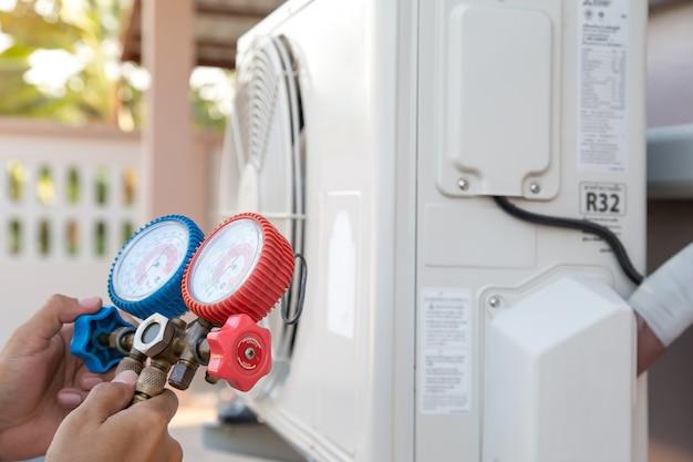 Luchtreparatiemonteur die manometerapparatuur gebruikt voor het vullen van de airconditioner in huis na reinigingsmiddelen. Premium Foto