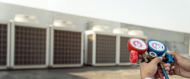 Luchtreparatiemonteur die meetapparatuur gebruikt voor het vullen van industriële fabrieksairconditioners voor onderhoud Premium Foto