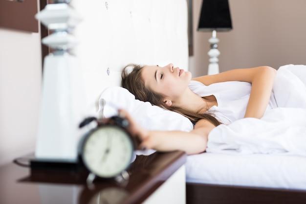 Luie vrouw blijft liggen nadat de wekker 's ochtends afging Gratis Foto
