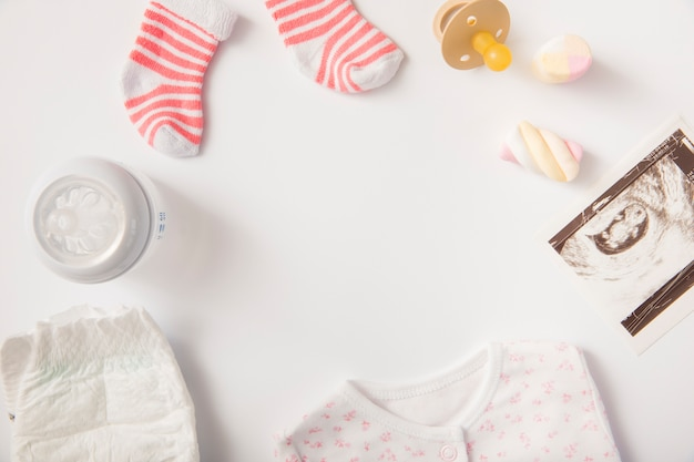 Luier; babykleren; heemst; sokken; fopspeen; echografie foto en melk fles op witte achtergrond Gratis Foto