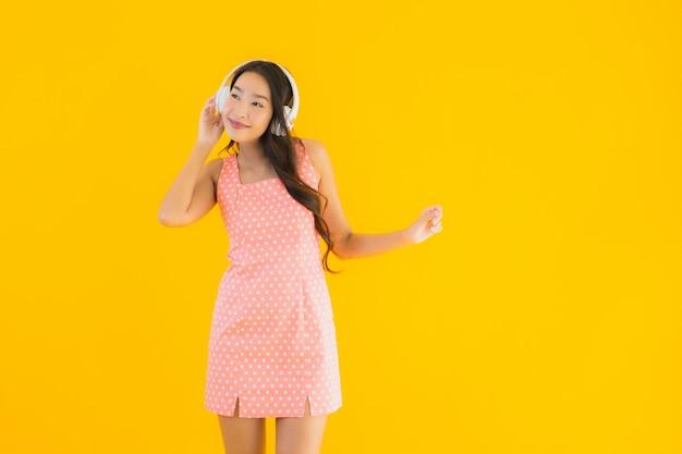 Luistert de portret mooie jonge aziatische vrouw muziek met hoofdtelefoon Gratis Foto