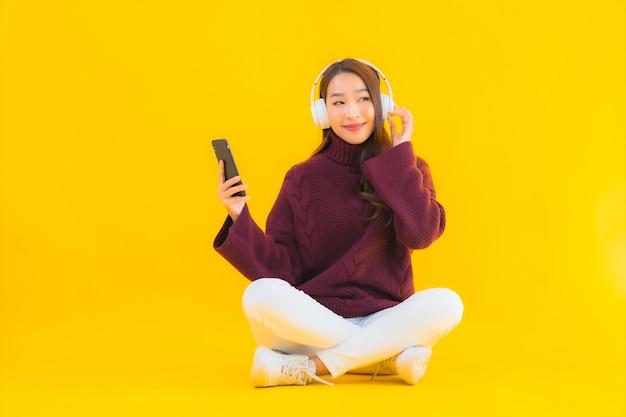 Luistert de slimme mobiele telefoon van de portret mooie jonge aziatische vrouw muziek Gratis Foto