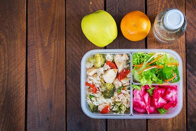 Lunchbox kip, broccoli, groene erwten, tomaat met rijst en rode kool. gezond eten. meenemen. lunchbox. bovenaanzicht Premium Foto