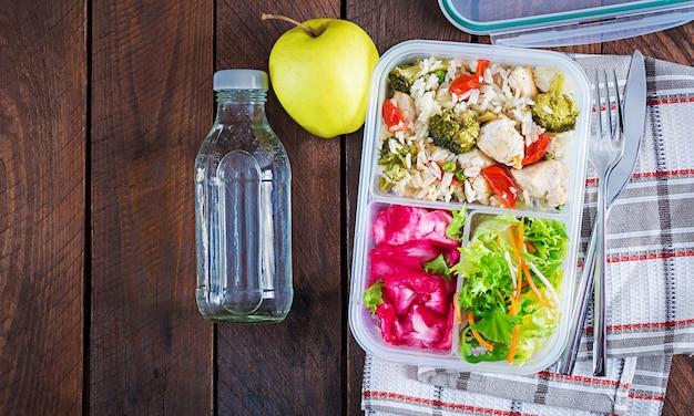 Lunchbox kip, broccoli, groene erwten, tomaat met rijst en rode kool Premium Foto