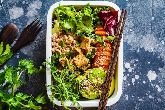 Lunchbox met gezond veganistisch eten. bentodoos met rijst, zoete aardappel, tofu en groenten. Premium Foto