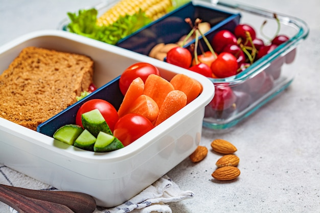 Lunchbox met gezond vers voedsel. sandwich, groenten, fruit en noten in een voedselcontainer, lichte achtergrond. Premium Foto
