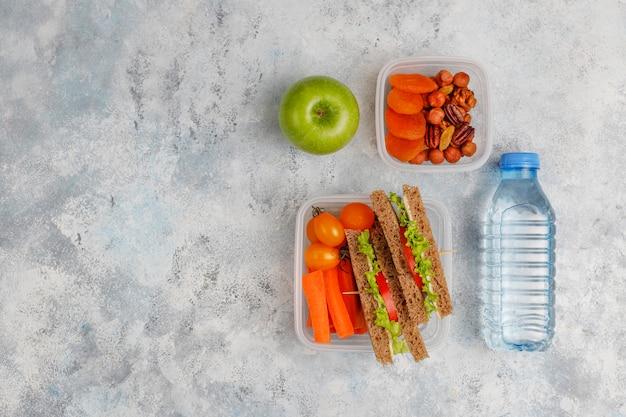 Lunchbox met sandwich, groenten, fruit op wit. Gratis Foto