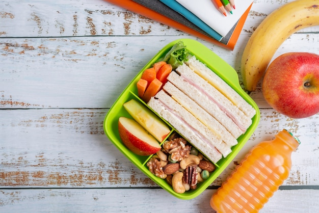 Lunchbox set ham kaas sandwich met wortel en gemengde noten, appel in doos, banaan en appel met sinaasappelsap. Premium Foto
