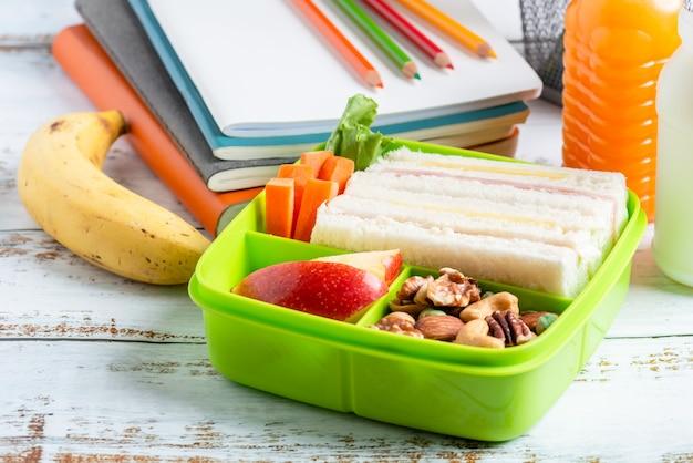 Lunchbox set ham kaas sandwich met wortel en gemengde noten, appel in doos, banaan en sinaasappelsap met melk. Premium Foto