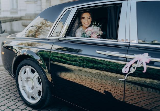 Luxe bruiloft. het schitterende elegante bruid stellen in modieuze luxe zwarte auto, die binnen in het boeket van de zaalholding zitten. Premium Foto