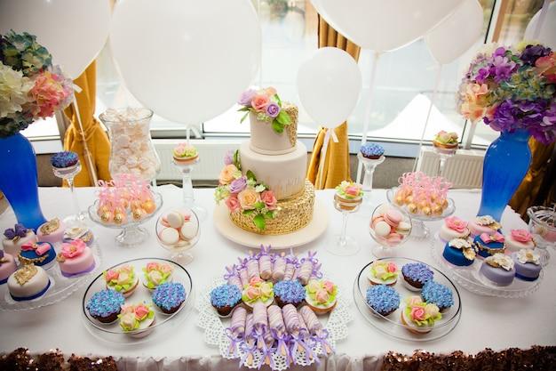 Luxe bruiloftscatering, tafel met moderne desserts, cupcakes, snoepjes met fruit. Premium Foto