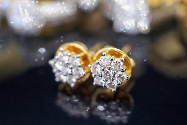 Luxe gouden sieraden diamanten oorbellen met reflectie op zwarte achtergrond Premium Foto