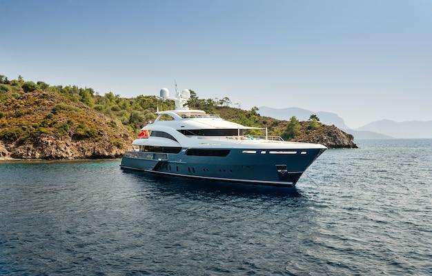 Luxe grote jacht verblijf in de zee rond het eiland op een achtergrond van de hemel Gratis Foto
